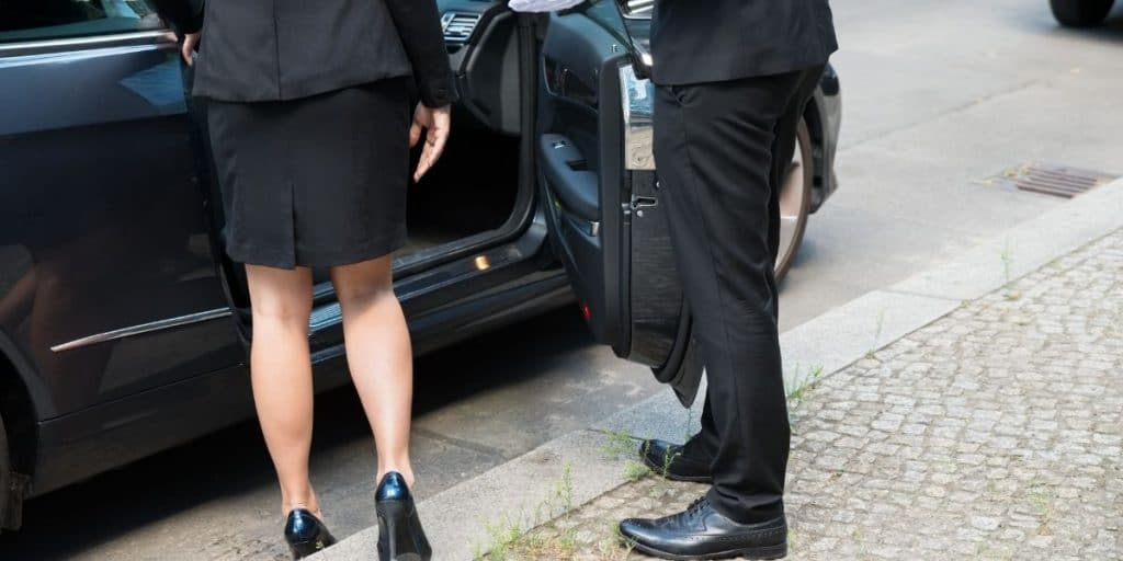 A chauffeur driver opened the door of the passenger