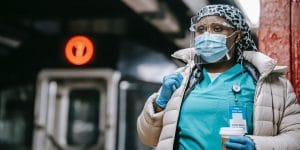 a photo of a female nurse in London wearing a face mask because of COVID